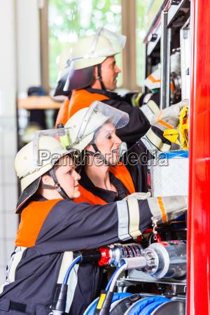 bomberos que fijan la manguera en