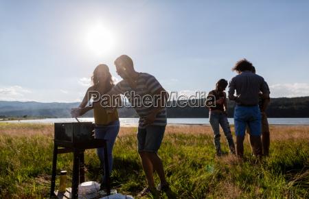 jovenes haciendo barbacoa en el lago