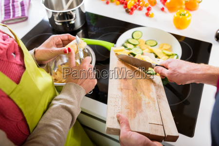 young couple cooking together in kitchen