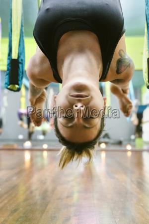 mujer practicando yoga aereo en clase
