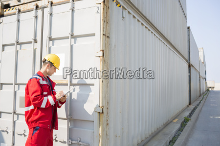 trabajador masculino inspeccionando contenedor de carga