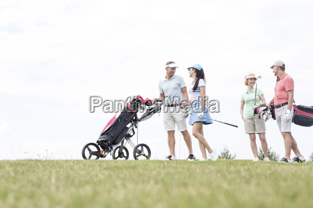 friends communicating while walking at golf