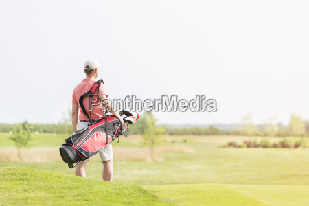 rear view of man carrying golf