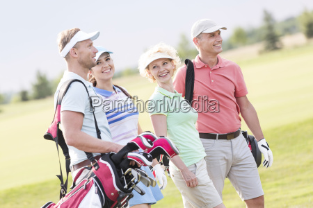 happy friends walking at golf course