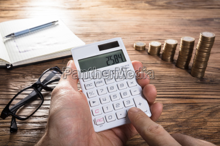 persona calculando ganancia en calculadora