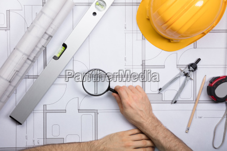 an engineer examining the architectural blueprint
