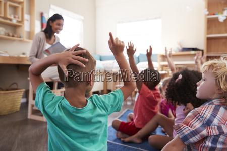 pupils at montessori school raising hands