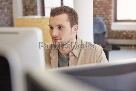young man sitting in office using