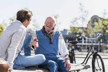 laughing senior man with adult grandson