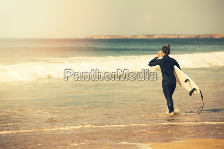 young surfer girl wearing wetsuit going