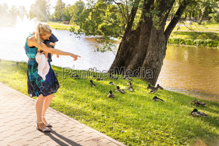 mother showing ducks to her baby