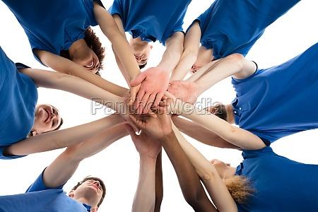 sonriendo conserjes multiraciales apilamiento manos