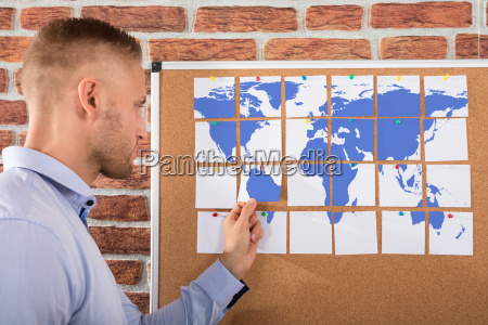 businessman looking at world map combined