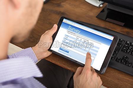 businessman filling survey form on digital