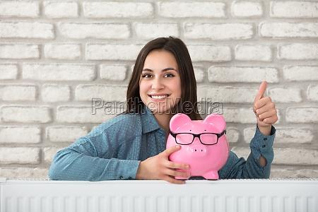 mujer sosteniendo piggy bank