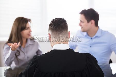 pareja peleando delante de juez