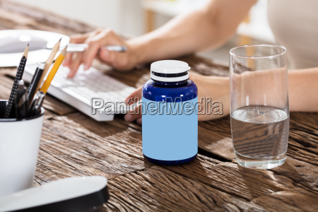 glass of water with pills bottle