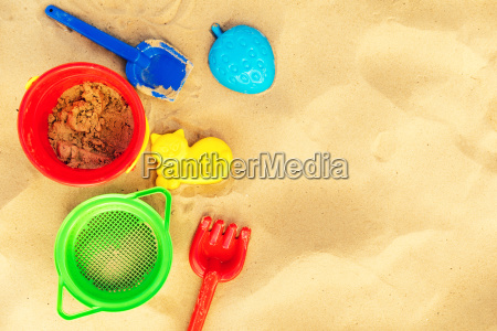 colorful beach toys on sand with