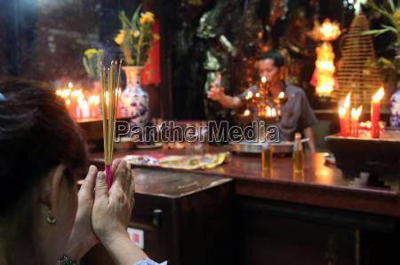 buddhist worshipper burning incense sticks taoist