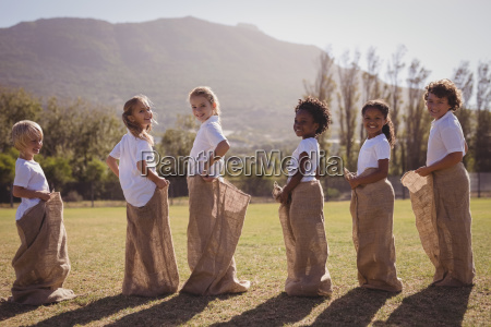 schoolgirls having fun during sack race