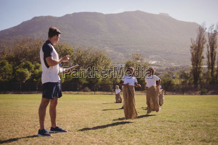 coach monitoring schoolgirls during sack race
