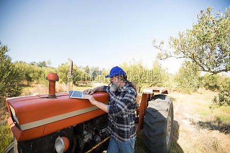 man using laptop in olive farm