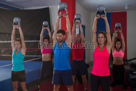 young athletes lifting kettles by boxing