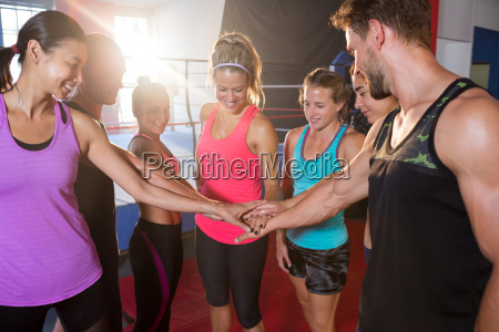 happy young athletes stacking hands against