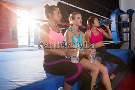 tired female athletes sitting with water