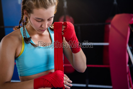 young female athlete wrapping red bandage