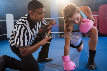 referee gesturing to female boxer in