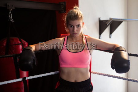 confident woman sitting in boxing ring