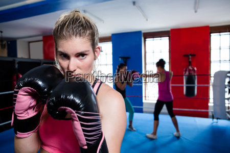young female boxer standing in ring