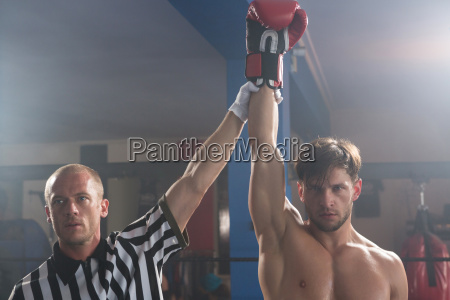 referee holding hand of winning young