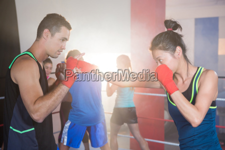 young female boxer practicing punch with