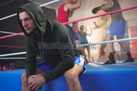 young male boxer sitting on boxing