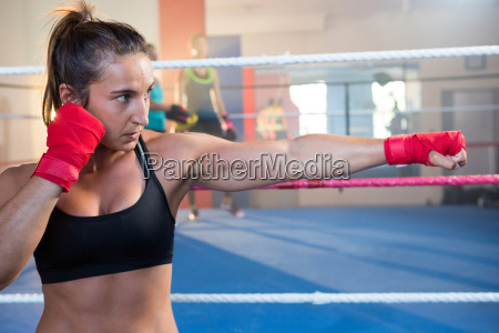 young female boxer punching against boxing