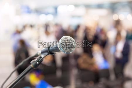 microfono en foco contra audiencia borrosa