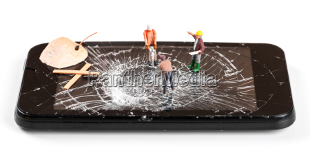 construction worker figurines repairing broken smartphone