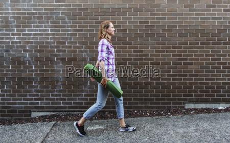 mujer joven caminando por la acera
