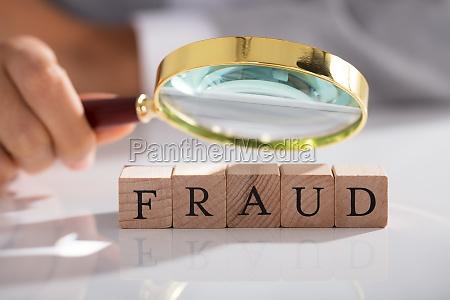 person, examining, fraud, blocks, through, magnifying - 23578602