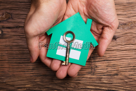 hands holding paper house with house