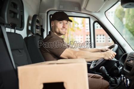 delivery man sitting inside van with
