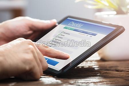 businessperson filling checklist form on digital