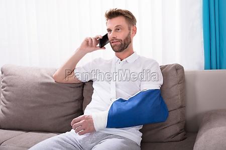 hombre con fractura mano hablando en