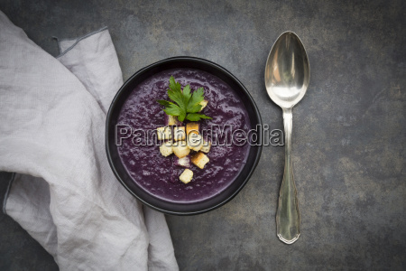 bowl of red cabbage soup garnished