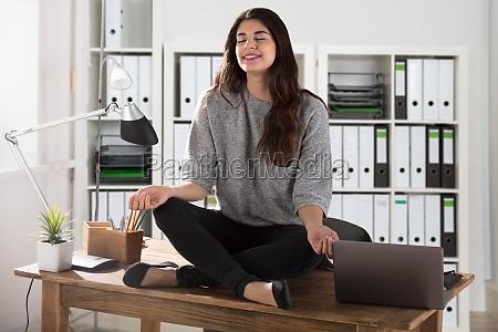 businesswoman meditando en oficina