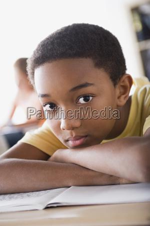 bored schoolboy leaning on desk