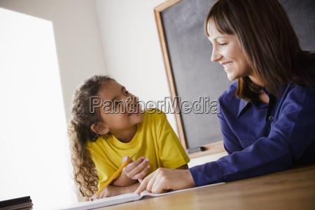 schoolgirl writing with teacher in classroom