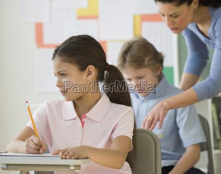 hispanic girl writing at school desk